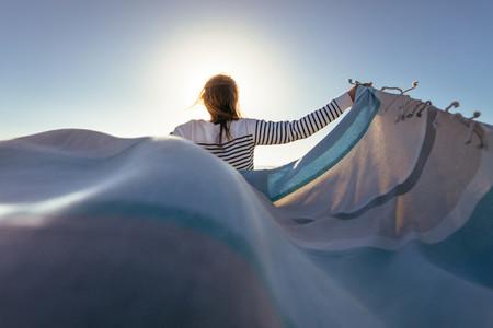 Woman standing holding a drape