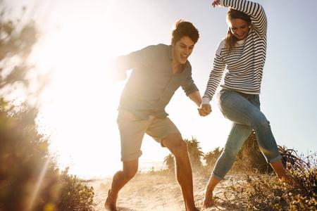 Happy man and woman running on the beach having fun