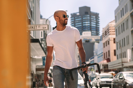 Handsome man in casuals walking outdoors with bicycle