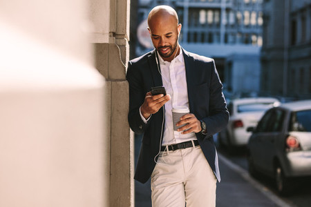 Businessman waiting outdoor using phone