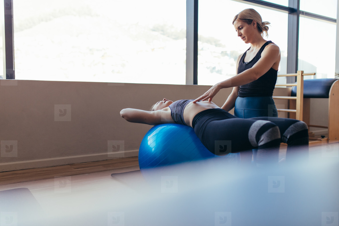 Woman training on exercise ball in a pilates training gym