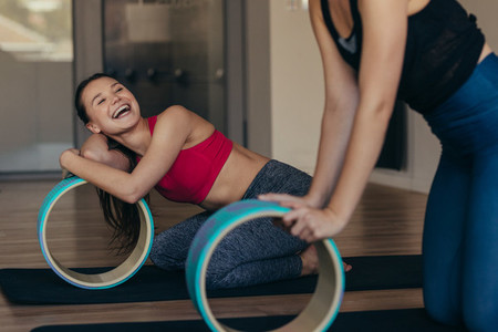 Pilates women at a gym holding a yoga or pilates wheel