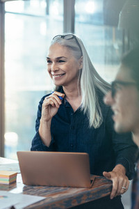Happy business woman in meeting with coworkers