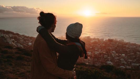 Romantic couple admiring the sunset from peak