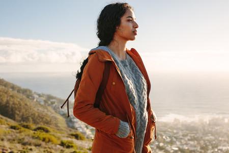 Woman in warm wear standing on a mountain looking away