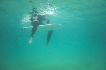 Underwater view of a surfer seated on his board waiting for a wave