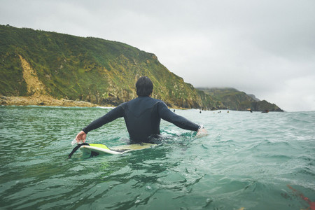 Back view of a surfer waiting for a wave in a cloudy winter day