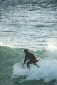 Mid aged surfer riding a wave on a sunny summer afternoon