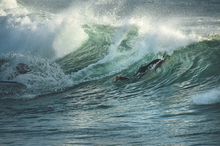 Mid aged surfer duck diving under a wave
