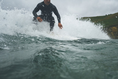 Mid aged man ridding a wave on a stormy day