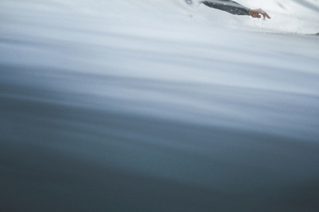Detail of hand of surfer surfing a wave abstract image