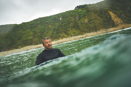 Mid aged man seated on his surf board waiting for a wave in a cloudy winter day