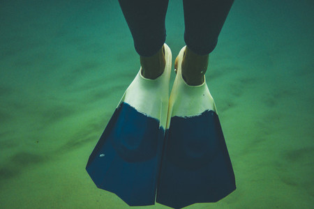 Close up of surfer fins underwater