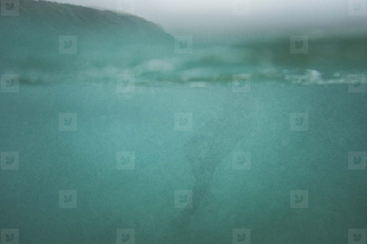 photos underwater silhouette of a surfer swimming in the ocean