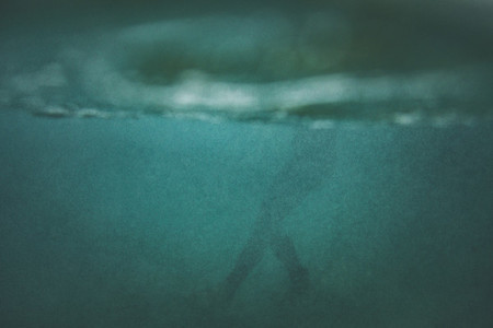 Underwater silhouette of a surfer swimming in the ocean surrounded by bubbles