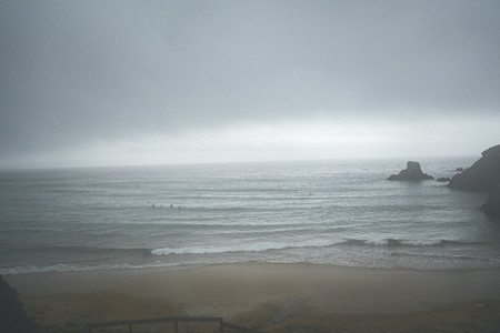 Group of four surfers waiting for a wave on a stormy winter day