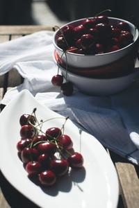 Dark cherries on white plate