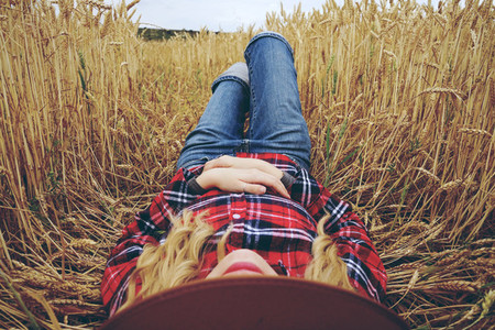 Young woman resting in a field of wheat