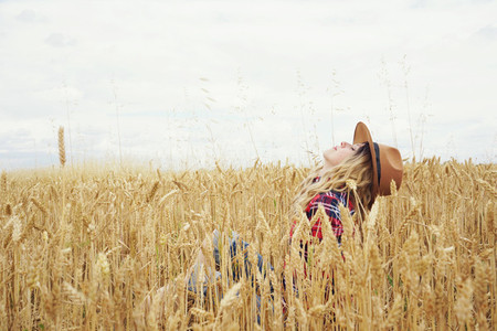 Young country woman in a field of wheat