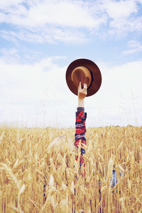 Back view of a young woman in a field of wheat