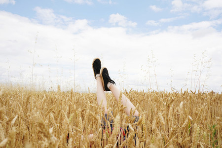 Child raised legs over a wheat field