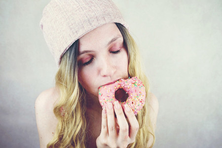 Young and funny blonde woman eating a donut