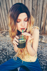 Blonde woman drinking a smoothie