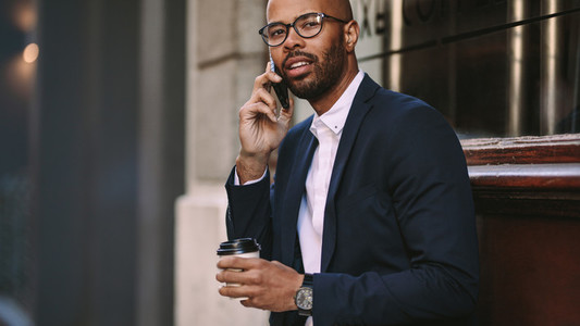 Man in business suit talking over cell phone outdoors