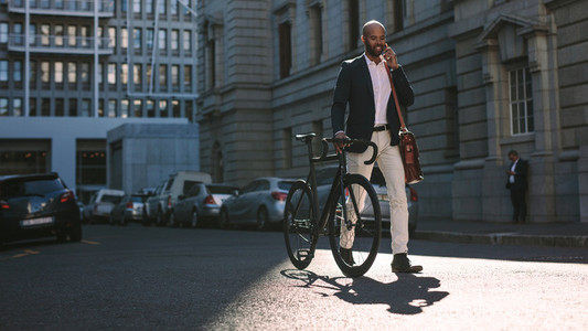 Businessman going to office by bicycle and talking on phone