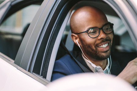 Man smiling inside the car while driving
