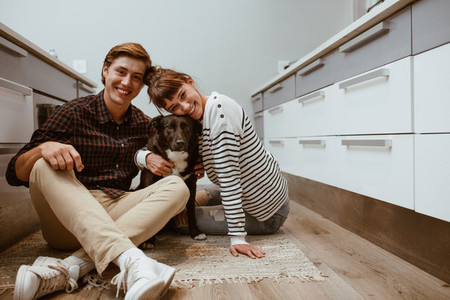 Happy couple at home with pet dog
