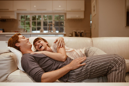 Smiling couple lying on a couch together