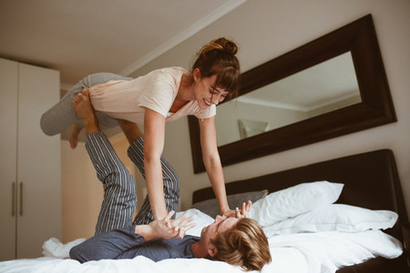 Couple having fun playing on bed at home