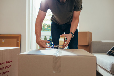 Man packing his household stuff in packing boxes and sealing the