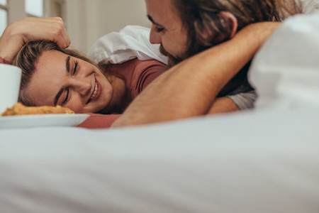 Close up of happy couple lying on bed looking at each other