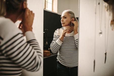 Female customer try on a designer ear ring at jeweler