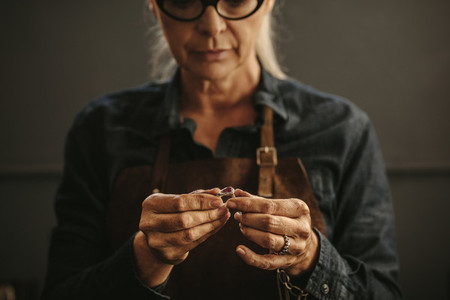 Woman goldsmith inspecting silver ring