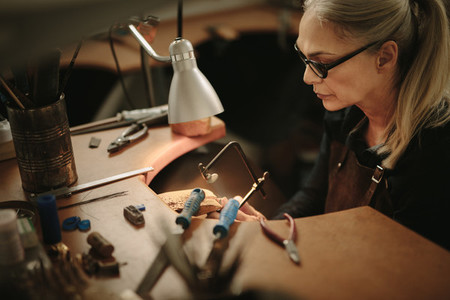 Female jeweler crafting metal in workshop