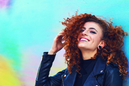 Redhead woman against color wall