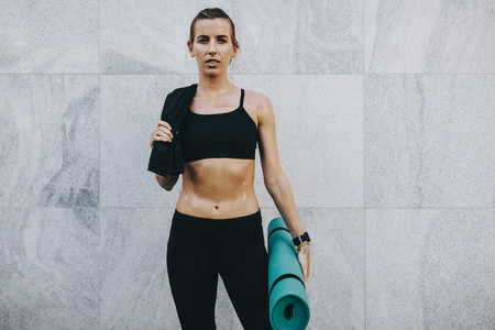 Fitness woman carrying her fitness mat and sweat shirt