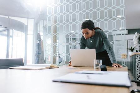 Businesswoman working on laptop in office boardroom
