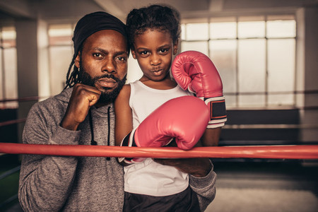 Coach with a boxer kid standing near a boxing ring