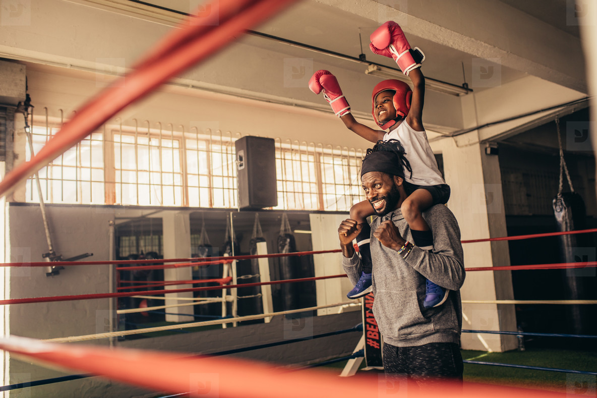 Happy boxer kid and coach celebrating victory standing inside bo