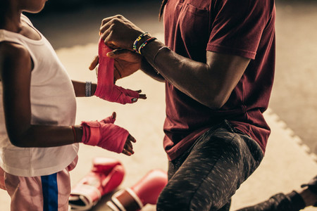 Boxing kid putting on bandages before wearing boxing gloves