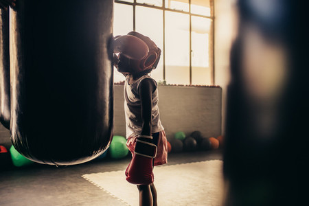 Boxing kid standing in front of a punching bag at a boxing gym