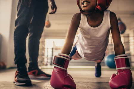 Boxing kid training inside a boxing gym with his coach