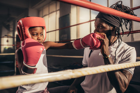 Boxing kid training with his coach at a boxing gym