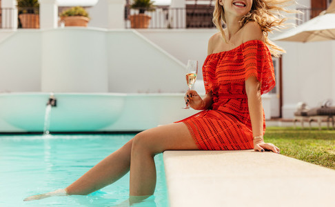Woman relaxing at the poolside of a luxury villa