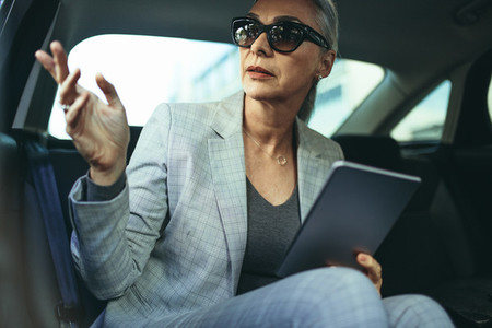 Mature businesswoman sitting on back seat of a car