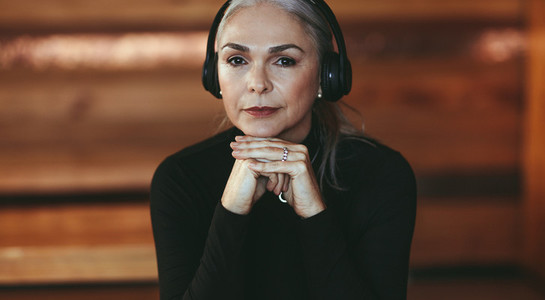 Senior woman listening to music in headphones at cafe